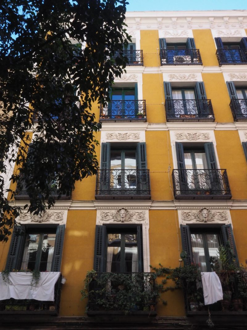 Spain Travel Inspiration - yellow building and balcony in Madrid during Autumn